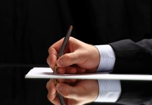 man's hand shown writing