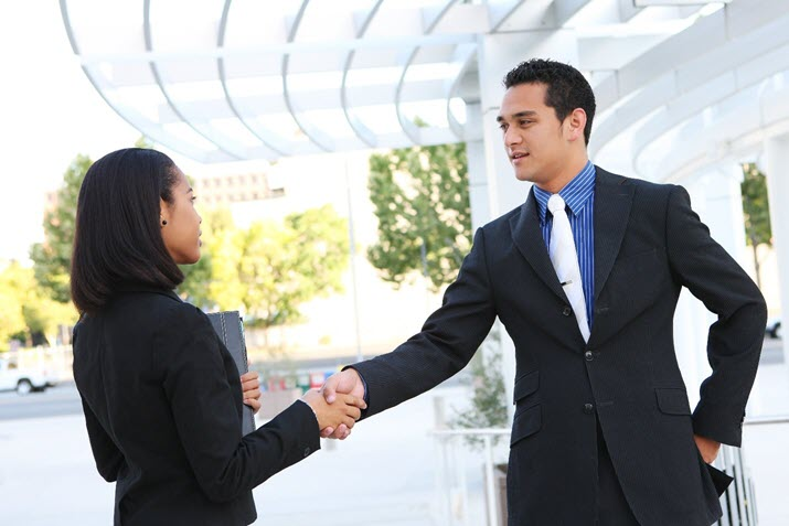 job seeker and employer shaking hands at in-person interview